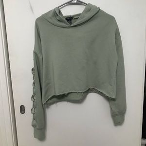 women's green cropped hoodie with design on sleeve